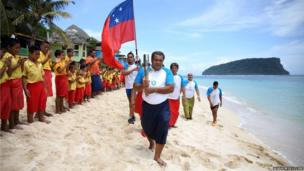 The Queen's baton touches down in Apia, Samoa and is carried down the beach by the Principal of Lalomanu primary school.