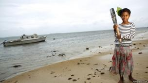 Christina Takitaki, holds the Queen's baton on the beach in Nuku'alofa, Tonga.