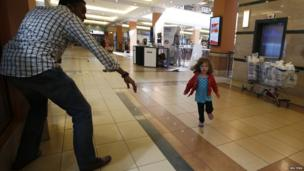 A child runs to safety as armed men hunt Islamist militants who went on a shooting spree at Westgate shopping centre in Nairobi - 21 September 2013
