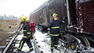 Firefighters use special foam to extinguish a fire on a diesel freight train en route to Manchester