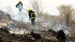 Crews survey the damage caused by a fire on Kersal Moor, Salford