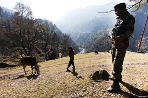 A Kashmiri Muslim girl walks as an Indian army soldier stands guard near the Line of Control with mountains of Pakistani side of Kashmir in the background, in Uri, some 125 km north of Srinagar