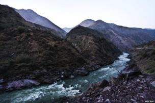 A stream passes through the mountains between Pakistani (left) and Indian (right) sides of Kashmir near the Line of Control near Kaman Post, 118 km north of Srinagar.