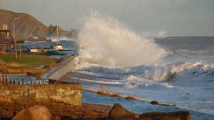 waves crashing against the sea defence at Cowie village near Stonehaven