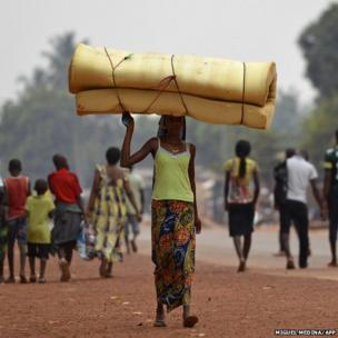 A woman carrying a mattress on her head flees the Gobongo district in Bangui on December 26, 2013