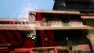A Gurung girl wearing a traditional costume watches a passing New Year parade from inside a cafe in Kathmandu
