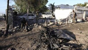 Soldiers assess the aftermath of a bomb explosion outside the Jazira hotel in the Somali capital Mogadishu
