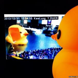 A rubber duck watches the giant inflatable duck deflating in Taiwan Port. Photo: Stanley_tw