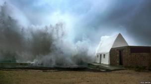 """Waves crashing into the Le Don Hilton building – known locally as the """"White House"""" - in St Ouen on the west coast of Jersey"""
