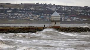 A man walks along the jetty at Porthcawl