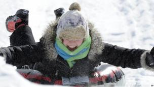 A girl takes a day off from school by taking advantage of an overnight snowfall to slide down a hill in Pringle, Pennsylvania
