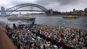 Members of the Australian cricket team wave to passengers sailing past on ferries during a public celebration ceremony at the Sydney Opera House, 7 January 2014