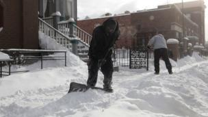 Workers in Detroit shovelling snow