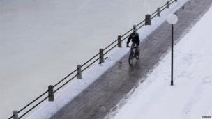 Man cycles next to Rideau Canal in Ottawa, Canada (6 Jan 2014)