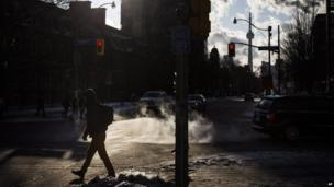 A man crosses the street in temperatures colder than -20F in Toronto