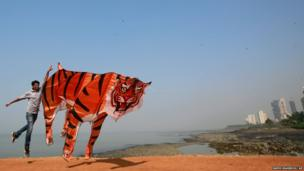 A participant runs with a large tiger-shaped kite as he prepares to fly it at the International Kite Festival in Mumbai, India