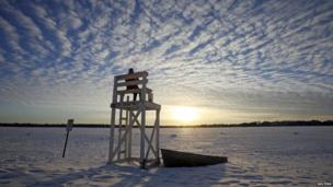 Jennifer Berry watches the sunset from a lifeguard chair at a beach on Lake Calhoun in Minneapolis.