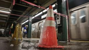 Water dripping into a New York subway station freezes on a warning cone
