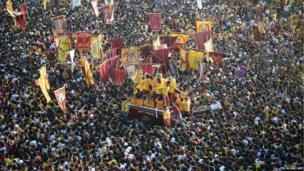 Sea of devotees clamber over one another to touch the Black Nazarene statue