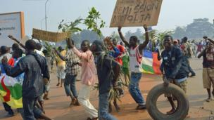 """Anti-Seleka demonstrators holding a placard reading """"Djotodia Resign"""" march to Mpoko airport on January 10, 2014 in Bangui, Central African Republic"""