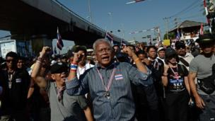 "Thai protest leader Suthep Thaugsuban (C) sings a song along with anti-government protesters as they march through the streets of Bangkok in a move to ""shut down"" the city on 13 January 2014"
