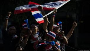 Anti-government protesters wave national flags during a rally in Bangkok