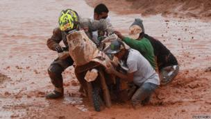 After falling from his motorbike, KTM rider Stephane Hamard of France gets help pushing his bike out of the water