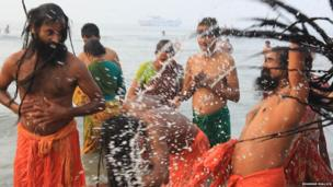 Hindu pilgrims dip in the water. Photo: Bhaskar Mallick