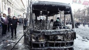 A protester sits in a burnt police bus after a rally near government administration buildings in Kiev 20 January 2014
