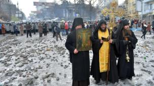 Orthodox priests pray as they stand between pro-European Union activists and police lines in central Kiev, Ukraine, Tuesday, 21 January 2014.