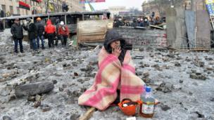 A protester smokes at the barricade in front of armour-clad security forces blocking access to the Verkhovna Rada parliament in Kiev on 21 January 2014