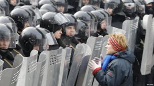 A woman addresses riot police with shields during a rally held by pro-European integration protesters in Kiev on 21 January 2014.