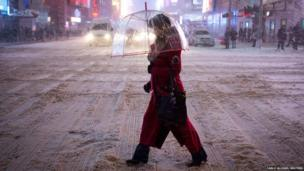 A woman carrying an umbrella walks along 42nd Street at Times Square during a snow storm in New York