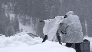 A member of Swiss special police forces manning a machine-gun on the roof of the Congress Centre in Davos