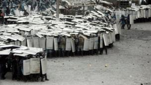 Riot police officers take cover behind shields during clashes with pro-European protesters in Kiev on Wednesday
