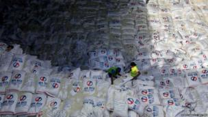 Workers unload rice imported from Vietnam from a ship docked at a port in Manila