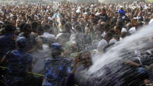 Ethiopian Orthodox worshippers are sprayed with baptism water in Addis Ababa on 19 January 2014