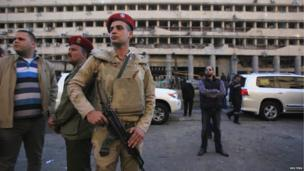 An army police officer stands guard in front of the damaged Cairo Security Directorate building, which includes police and state security, after a bomb attack in downtown Cairo, 24 January 2014