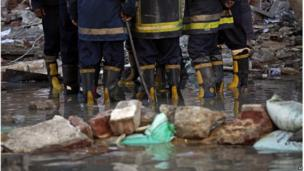 Egyptian fire fighters check the damage at the site of a blast at the Egyptian police headquarters in downtown Cairo, Egypt, Friday, 24 Jan 2014.