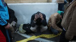 Egyptian police officers sit on the street after a blast at the Egyptian police headquarters in Cairo