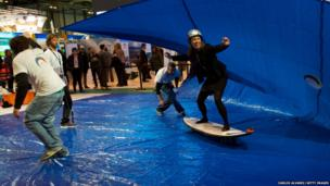 A visitor rides an artificial wave