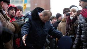 Interior ministry official in Ivano-Frankivsk bows his head to protesters after leaving the regional administration HQ (25 Jan)