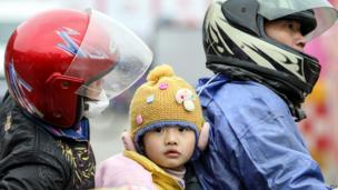 Shunning China's overcrowded public transport during the world's largest migration, this family join an estimated 600,000 people heading home on the highways. Here arriving on a motorcycle at a pit stop in Wuzhou, Guangxi province