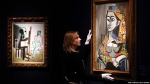 A Christie's employee poses besides Femme au costume turc dans un fauteuil by Pablo Picasso in London