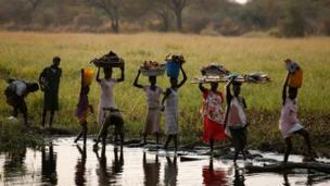 People cross a river in a rebel-controlled territory in Jonglei State