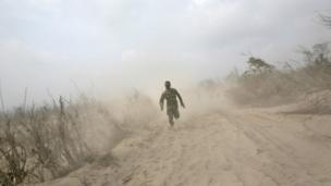 An Indonesian soldier runs on ash-covered road as he and his team search victims of the eruption of Mount Sinabung in Suka Meriah, North Sumatra, Indonesia, Sunday, 2 February 2014