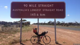Bike propped up against a sign saying 'Australia's longest road'