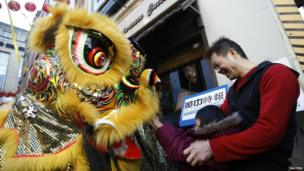 A father and daughter react to a Lion Dance performance at the entrance to a restaurant