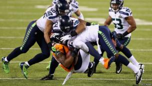 Demaryius Thomas of the Denver Broncos is tackled during Super Bowl