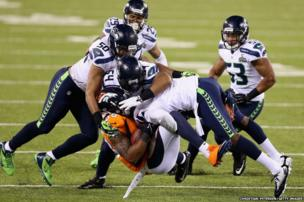 Wide receiver Demaryius Thomasof the Denver Broncos is tackled during Super Bowl XLVIII against the Seattle Seahawks